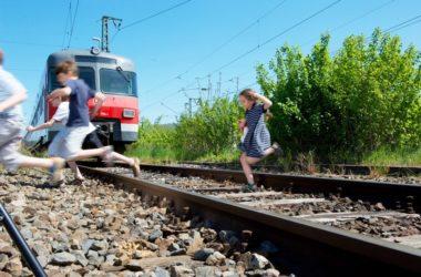Kinder laufen über Gleis
