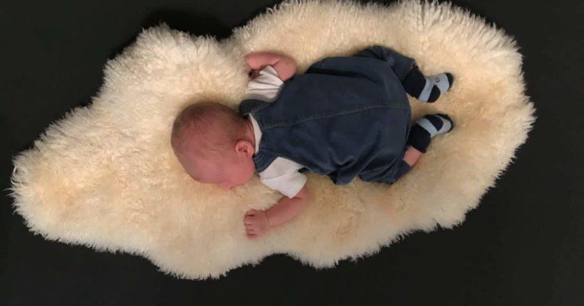 Baby leigt auf Fell